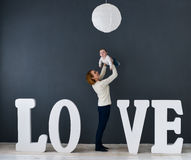 Behandla som ett barn den lyckliga modern för ståenden och, på grå bakgrund nära stora bokstäver av ordförälskelsen Arkivfoto