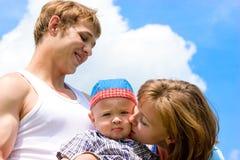 behandla som ett barn den lyckliga over skyen för den blåa familjen Royaltyfria Bilder