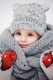 Behandla som ett barn den nära övre vertikala ståenden för vintern av förtjusande le flickan i grå färger stucken hatt och halsdu Arkivbild