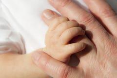 behandla som ett barn den nyfödda handen Arkivfoton