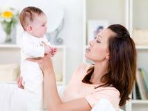 behandla som ett barn den nyfödda kvinnan för holdingen Royaltyfria Foton