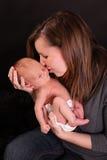 behandla som ett barn den nyfödda kyssande modern Arkivfoton