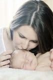 behandla som ett barn den nyfödda kyssande modern royaltyfri fotografi