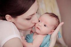 behandla som ett barn den nyfödda kyssande modern Royaltyfria Bilder