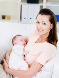 behandla som ett barn den nyfödda slepping kvinnan för holdingen Arkivbilder