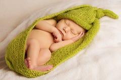 Behandla som ett barn den nyfödda ståenden, ungen som sover i woolen Arkivbild
