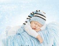 Behandla som ett barn den nyfödda hattdräkten, den nyfödda ungen som sover på den blåa filten Arkivbild