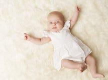 Behandla som ett barn den nyfödda ståenden, nyfödd flicka en månad, den vita klänningen för ungen Arkivfoton