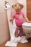 behandla som ett barn den paper toaletten för flickan Arkivbilder