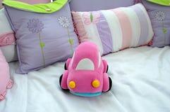 behandla som ett barn den rosa toyen för bilen Arkivfoton