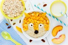 Behandla som ett barn den söta sunda frukosten - mjölka havremjölhavregröt med persikan Arkivfoto