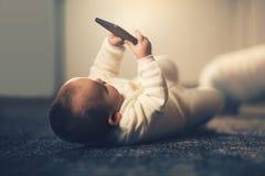 Behandla som ett barn den smarta telefonen för innehavet Royaltyfri Bild