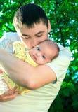 behandla som ett barn den stiliga fadern kyssa little Arkivfoto