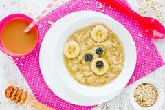 Behandla som ett barn den sunda frukosten - havremjölhavregröt med honung och bananen Arkivfoto