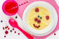 Behandla som ett barn den sunda frukosten - majshavregröt med bäret i form arkivbild