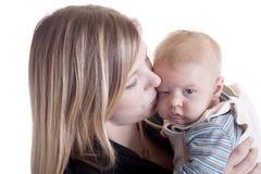 behandla som ett barn den tröttade kyssande modern Royaltyfri Bild