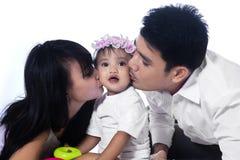 behandla som ett barn deras kyssande föräldrar Arkivbilder
