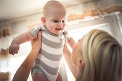 Behandla som ett barn det hemmastadda innehavet för modern hennes litet pojken close upp royaltyfria bilder