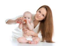 Behandla som ett barn det matande barnet för modern från flaskan med vatten Royaltyfria Foton