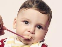 Behandla som ett barn det matande spädbarnet för moderhanden mat arkivfoto