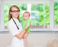 Behandla som ett barn det pediatriska och tålmodiga barnet för den lyckliga kvinnliga doktorn Royaltyfria Bilder