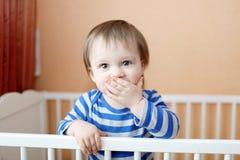 Behandla som ett barn det tysta anseendet för uppehällen i vit säng Fotografering för Bildbyråer