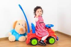 Behandla som ett barn det vinkande farvälet för flickan på en leksakbil arkivbilder