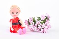 Behandla som ett barn - docka- och rosa färgblommor Arkivbild