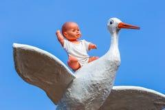 Behandla som ett barn - dockasammanträde på baksida av storken med blå himmel Arkivfoton