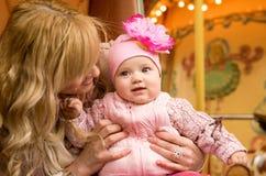 behandla som ett barn dottern går henne den runda glada modern Royaltyfria Bilder