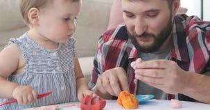 Behandla som ett barn dottern som lär att spela med plasticine lager videofilmer