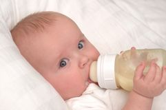 behandla som ett barn dricka månad gammala sex för flaskpojken Arkivfoton
