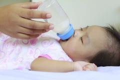 Behandla som ett barn drinken mjölkar och sover Arkivbilder