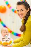 behandla som ett barn födelsedagcaken bär momen till Arkivfoto