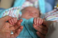 behandla som ett barn faderhänder Arkivfoto