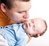 behandla som ett barn fadern hans nyfödda kyssar Arkivfoto