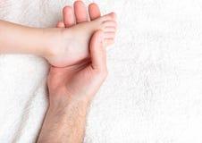 behandla som ett barn fadern rymmer försiktigt ben s Arkivbild