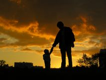 behandla som ett barn fadersolnedgången royaltyfri bild