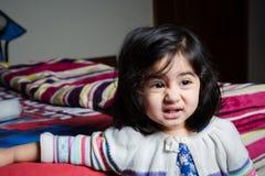 Behandla som ett barn flickaanseendet vid sängen Royaltyfria Bilder