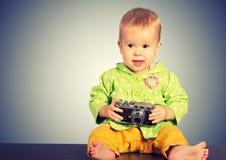 Behandla som ett barn flickafotografen med den retro kameran Arkivfoto