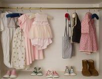 Behandla som ett barn flickagarderoben med den hängande klänningen & kängor royaltyfri bild