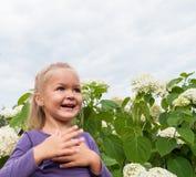Behandla som ett barn flickagyckel som spelar i vita blommor Royaltyfri Fotografi