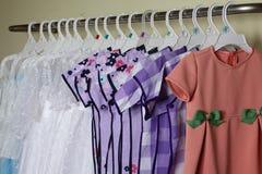 Behandla som ett barn flickakläder som hänger på klädstreck Arkivfoton