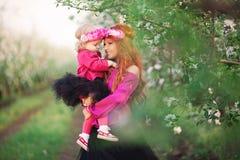 Behandla som ett barn flickakvinnan i vårträdgårdar som blommar Fotografering för Bildbyråer