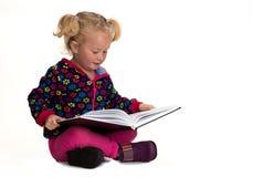 Behandla som ett barn flickaläsning Arkivbild