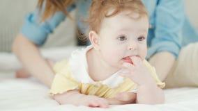 Behandla som ett barn flickalögner på hennes mage på sängen, mamma kysser hennes dotter arkivfilmer