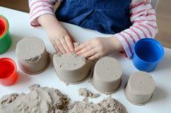 Behandla som ett barn flickalek med kinetisk sand Royaltyfri Foto
