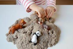 Behandla som ett barn flickalek med kinetisk sand Arkivbilder