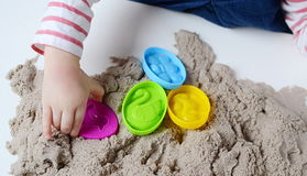 Behandla som ett barn flickalek med kinetisk sand Arkivfoton