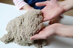 Behandla som ett barn flickalek med kinetisk sand Arkivfoto
